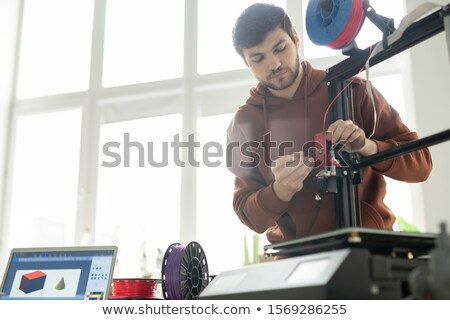 Young technician repairing or changing printhead while fixing its details Stock photo © pressmaster