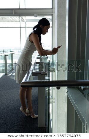Side view of young businesswoman leaned on the railing and chating on his mobile phone on first floo Stock photo © wavebreak_media