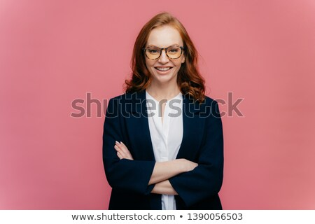 Half length shot of ginger business lady satisfied after conference, keeps arms folded, wears optica Stock photo © vkstudio