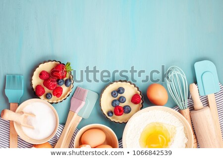 Sweet tart with berries on table with ingredients and utensils Stock photo © dashapetrenko
