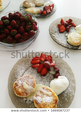 Curd berry dessert on a plate sprinkled with powdered sugar next to fresh strawberries Stock photo © ElenaBatkova