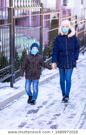 Young woman with little boy wearing medical face masks to protect themselve from pollution, germs an Stock photo © Len44ik