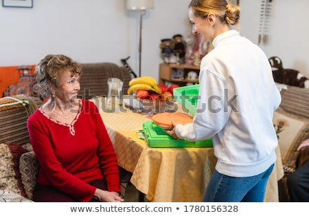 Volunteer serving a meal to senior woman in assisted living program Stock photo © Kzenon