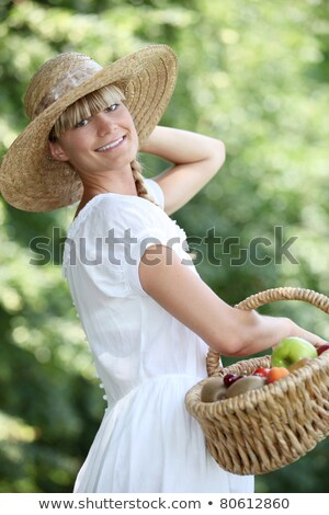 Carefree woman with a straw hat and wicker basket full of fruit Stock photo © photography33