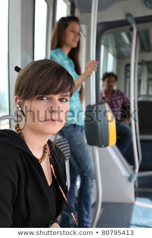 Photo of teenager riding the tram with passenger in background Stock photo © photography33
