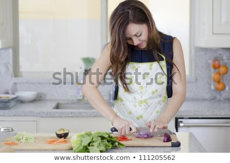 Brunette chopping vegetables in the kitchen Stock photo © photography33