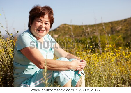 happy smiling asian woman sit on ground stock photo © elwynn