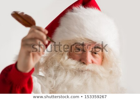 Santa Claus holding feather pen in his arm and writing  Stock photo © HASLOO