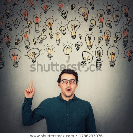 Businessman Looking At Floating Lightbulb stock photo © jackethead
