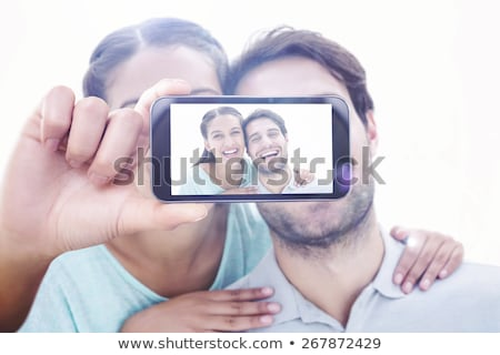Composite image of happy brunette holding smartphone Stock photo © wavebreak_media