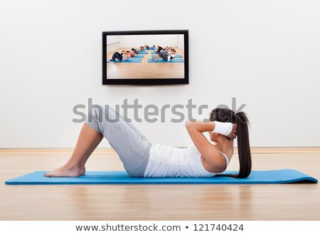 Athletic young woman working out at home lying on a mat doing liftups Stock photo © deandrobot