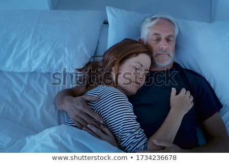 woman on bed while man sleeping in bedroom stock photo © andreypopov