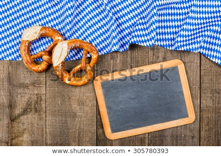 Pretzel with bavarian tablecloth on a wooden background Stock photo © Zerbor