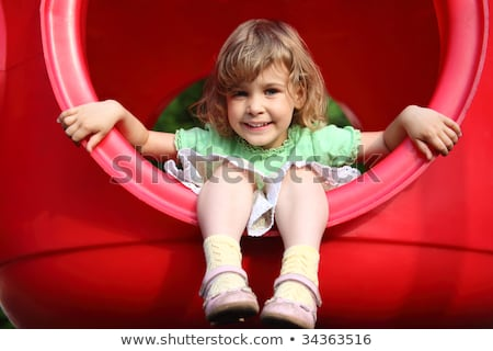 little girl sits in red plastic hole on playground Stock photo © Paha_L