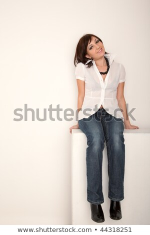 Smiling girl in jeans and white shirt sitting in white studio. Vertical format. Stock photo © Paha_L