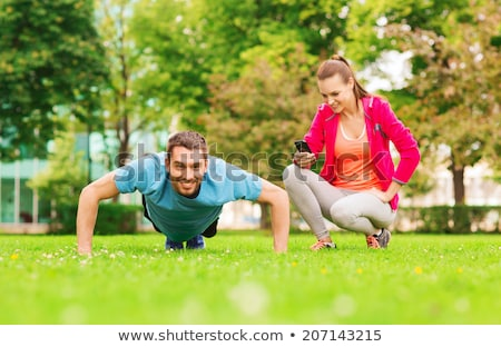 Smiling young woman and personal trainer with smartphone outdoors Stock photo © deandrobot