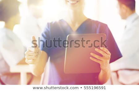 close up of nurse with tablet pc showing thumbs  stock photo © dolgachov