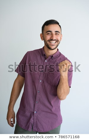 Young man clenching fists in winning gesture Stock photo © Giulio_Fornasar