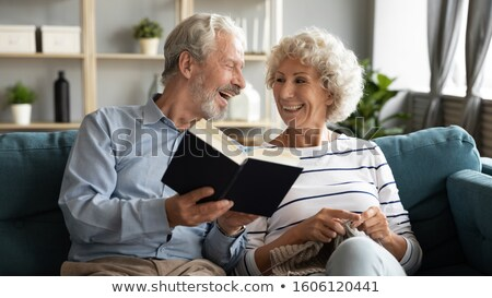 woman reading book to senior man Stock photo © IS2