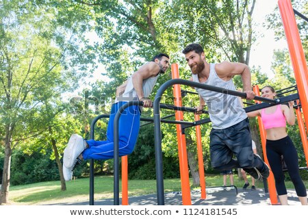 Two muscular young men doing bodyweight exercises in fitness park Stock photo © Kzenon