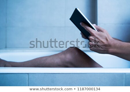 man reading in bathtub in a mysterious atmosphere