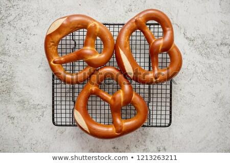 three german fresh baked pretzel buns placed on steel grill frame stock photo © dash