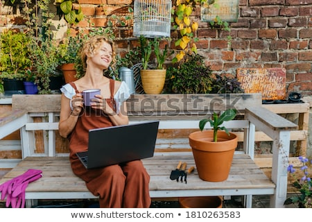 Woman gardener sitting over flowers plants in greenhouse. Stock photo © deandrobot