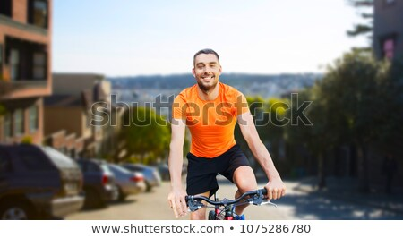 happy man riding bicycle over san francisco city Stock photo © dolgachov