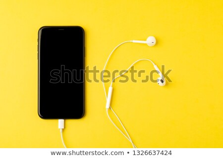 Smartphone and wired earphones on yellow background Stock photo © magraphics