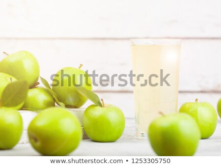 Glass of fresh organic apple juice with green apples in box on wooden background with sun light stock photo © DenisMArt