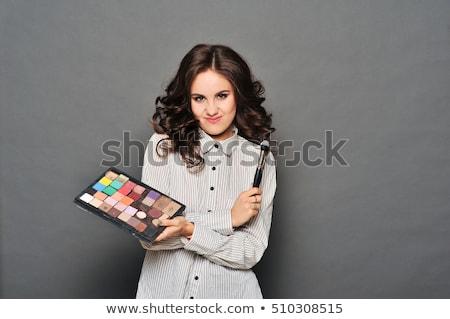 Stock photo: makeup artist paints a very pretty brunette