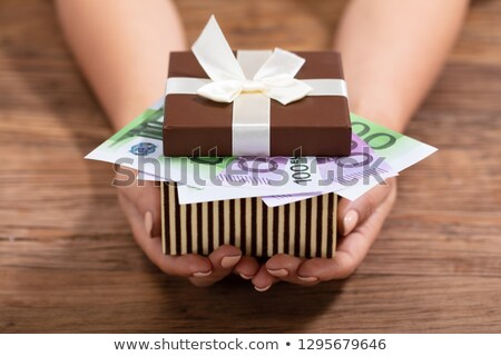 hand holding gift box filled with euro notes stock photo © andreypopov