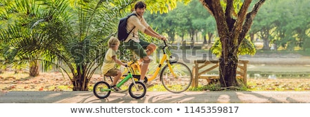 Stockfoto: Happy Family Is Riding Bikes Outdoors And Smiling Father On A Bike And Son On A Balancebike Banner