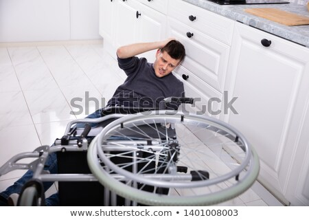 disabled man fallen out of his wheelchair on floor stock photo © andreypopov