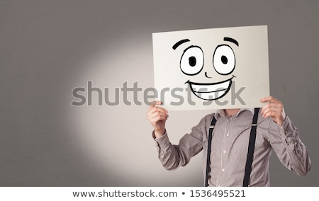 Student holding a paper with laughing emoticon in front of his face Stock photo © ra2studio