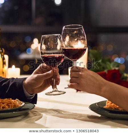 hands of couple with red wine glasses toasting stock photo © dolgachov