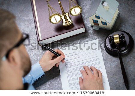 Judge With House Model Writing On Paper Stock photo © AndreyPopov