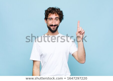 Image of young bearded man smiling and pointing finger upward Stock photo © deandrobot