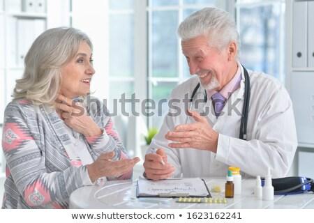 senior lady doctor posing with stethoscope stock photo © stockyimages