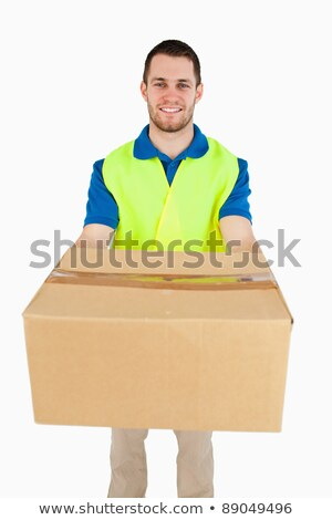 Smiling young delivery man carrying a parcel against a white background Stock photo © wavebreak_media