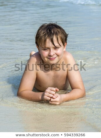 boy enjoys lying in the spume of the tropical beach  Stock photo © meinzahn