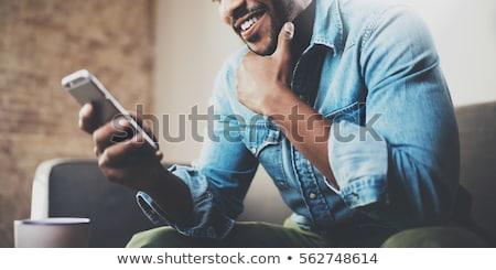glimlachend · aantrekkelijk · jonge · zakenman · permanente · smartphone - stockfoto © lithian