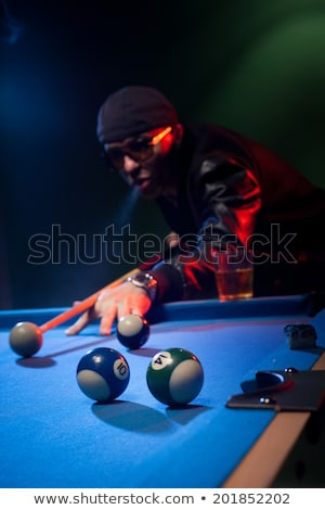 Trendy pool player in a leather jacket and cap Stock photo © stryjek