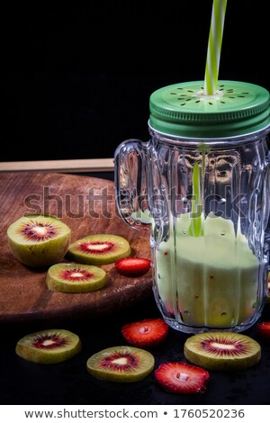 Strawberries and halved kiwifruits Stock photo © leowolfert