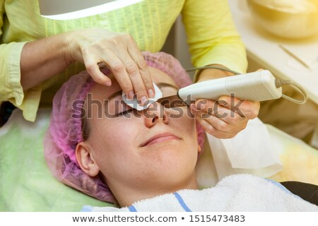 woman under procedure of ultrasonic facial cleaning stock photo © d13