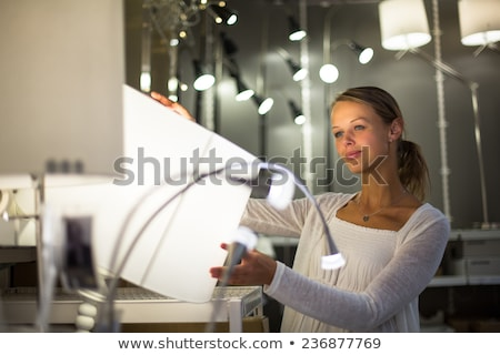 pretty young woman choosing the right light for her apartment stock photo © lightpoet