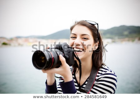 Happy woman photographer holding camera Stock photo © deandrobot
