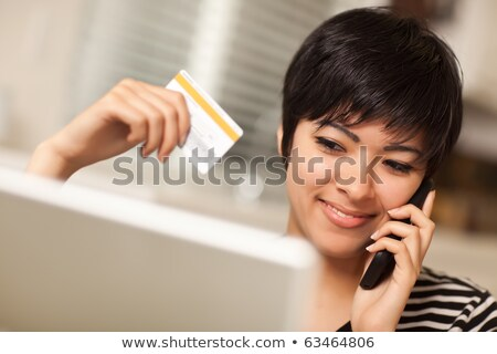 Foto stock: Multiethnic Woman Holding Phone And Credit Card Using Laptop