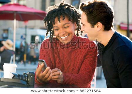 close up portrait of couple looking at phone in cafe stock photo © deandrobot