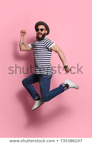 vertical image of hipster jumping at camera stock photo © deandrobot